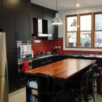 Magnificent black cabinet doors with red tiled splashback area and stainless steel benchtop